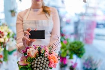 Hände, die Design-Raum-leere Karte mit Blumen-Blumenstrauß halten