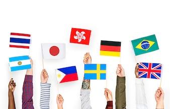 Hände, die internationale Flaggen halten