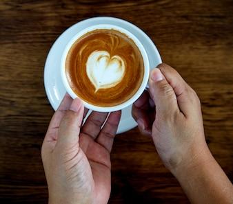 Hände, die Kaffeetasse-Herzschale halten