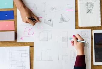 Hände, die Zeichnung auf Ideen-Papier-Arbeiten schreiben