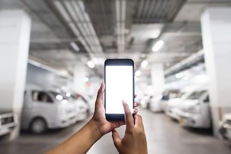 Hände halten den leeren weißen Bildschirm Smartphone auf dem Parkplatz