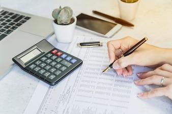 Hände mit Stift, die Tabelle auf Papier überprüfen