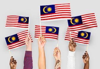 Hände wehende Fahnen von Malaysia