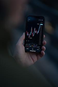Handeln sie, wo immer sie sind. männliche hand mit mobiler app auf dem smartphone zum lesen von finanznachrichten in echtzeit und zum überprüfen von börsendaten in echtzeit. selektiver fokus auf dem bildschirm mit forex-grafikdiagramm