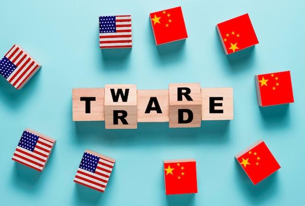 Handelskriegsformulierung auf holzwürfelblock mit usa- und china-flagge. es ist symbol des wirtschaftlichen zollhandelshandelskriegs und der steuerbarriere zwischen den vereinigten staaten von amerika und china.