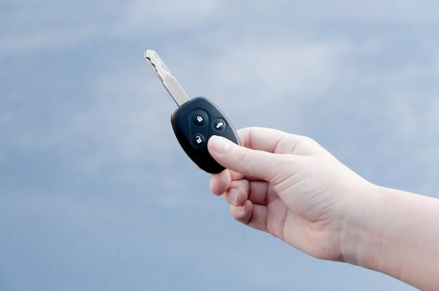 Handfrau, die autoschlüssel hält, frauenhand, die schlüssel gibt