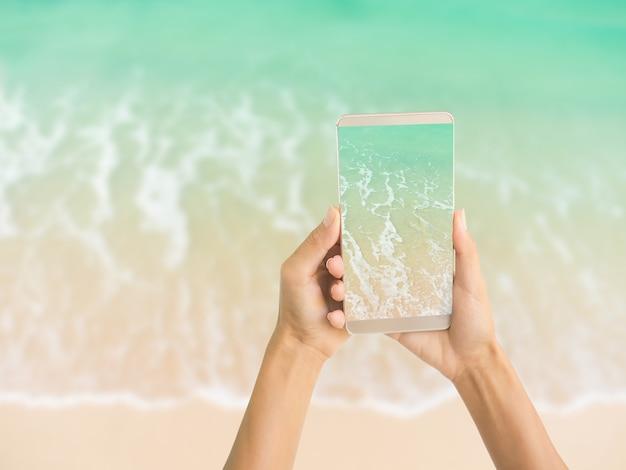 Handfrau, die den blauen meersandstrand der mobilen ansicht auf unschärfebild der strandmeerwellen, sommer in den ferien hält