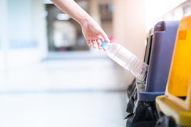 Handfrau, die die flasche hält, wirft sie in den abfall.