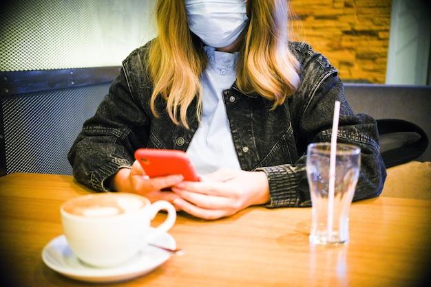 Handfrau, die ein bild der heißen latte-kunstkaffeetasse auf holztisch mit ihrem smartphone nimmt, das an einem kaffeehaus sitzt.