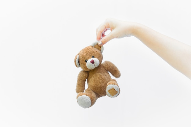 Handfrau, die ohr braunes teddybärspielzeug auf weißem hintergrund hält