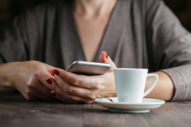 Handfrau, die telefon und tasse kaffee hält