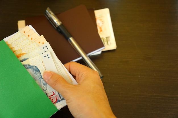 Handfrauengriff die singapur-dollar im grünen umschlag