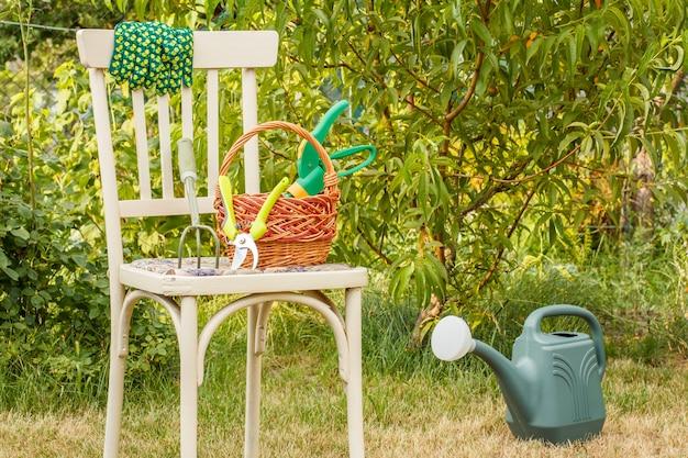 Handgartenrechen, gartenschere, handschuhe und weidenkorb auf altem stuhl, gießkanne auf gras im natürlichen hintergrund. gartengeräte und pflanzen.