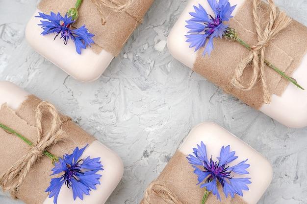 Handgearbeitetes naturseifenset, verziert mit kraftpapier, geißel und blauen blumen. bio-kosmetik-konzept.