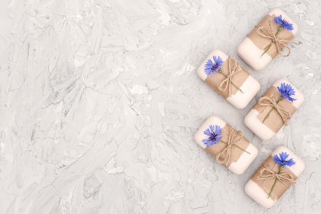 Handgearbeitetes naturseifenset, verziert mit kraftpapier und blauen blumen