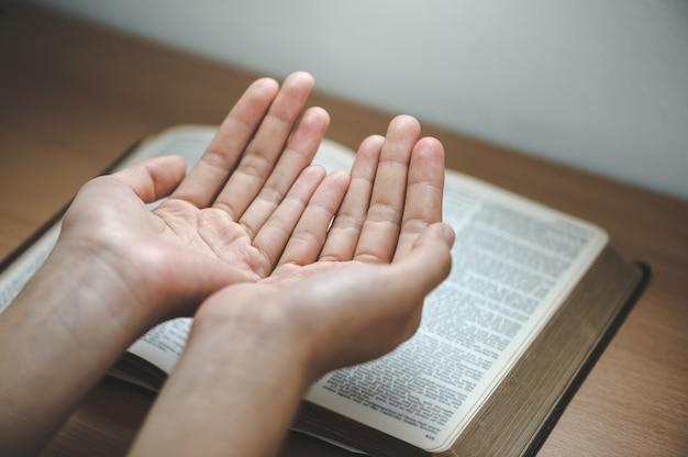 Handgebet auf einer heiligen bibel im kirchenkonzept für glaubensspiritualität und religion