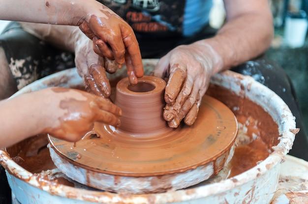Handgefertigt, hände machen ton. der meister lehrt den schüler, krug auf der töpferscheibe zu machen.