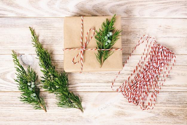Handgefertigte geschenkbox auf rustikalem weißem hölzernem mit weihnachtsdekorationstannenbaum