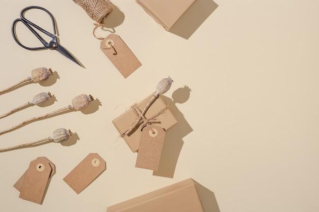Handgefertigte geschenkboxen aus kraftpapier mit tags verziert mit natürlicher trockener mohnblume