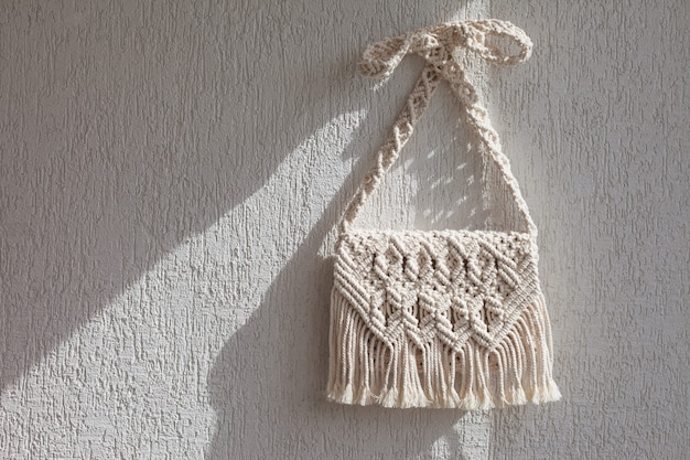 Handgefertigte makramee-tasche an der hellen wand.