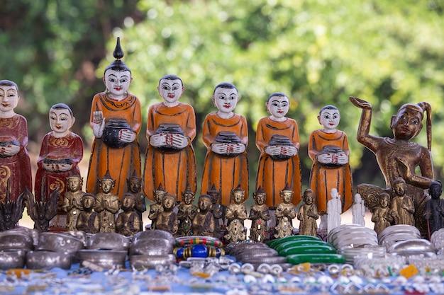 Handgefertigte mönchsfigur und anderes souvenir in einem touristenstand auf dem straßenmarkt in der nähe des inle-sees in burma. nahaufnahme. souvenirartikel zum verkauf in myanmar