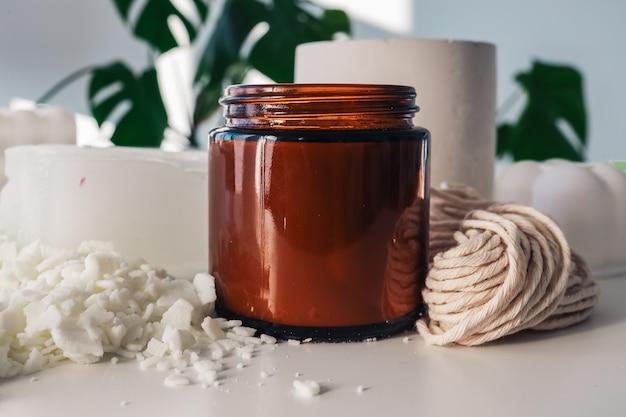 Handgefertigte ökologische und vegane sojawachskerzen mit holzdocht. bernsteinfarbener und undurchsichtiger behälter. mock-up, platz für text.