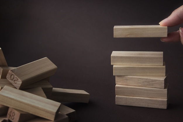 Handgefertigter holzblock im turm, der den bauerfolg symbolisiert. startup-konzept der unternehmensorganisation, konzept für soziale netzwerke.