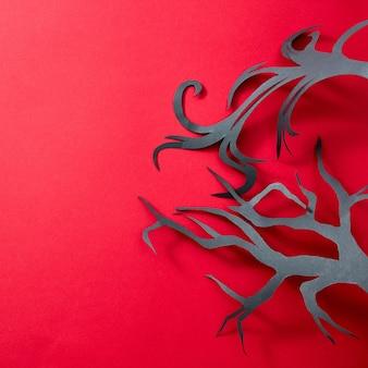 Handgefertigter schwarzer baum aus papier auf rotem hintergrund mit reflexion von schatten und kopierraum für text. kreatives halloween-layout. flach liegen