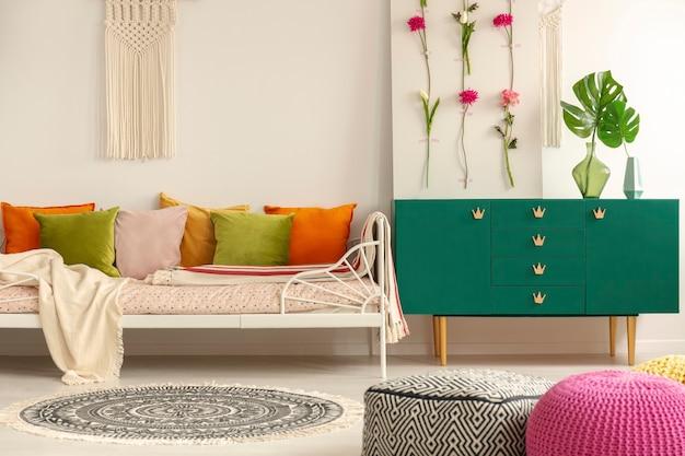 Handgefertigtes blumenbrett auf grünem holzschrank mit blatt in glasvase neben bequemem bett mit olivgrünen, pastellrosa, gelben und orangefarbenen kissen