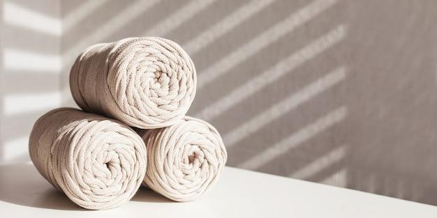 Handgefertigtes makramee-geflecht und baumwollfäden. hobby-strickgarnrolle aus baumwolle. natürliche baumwollkordel. weibliches hobby. platz kopieren. banner