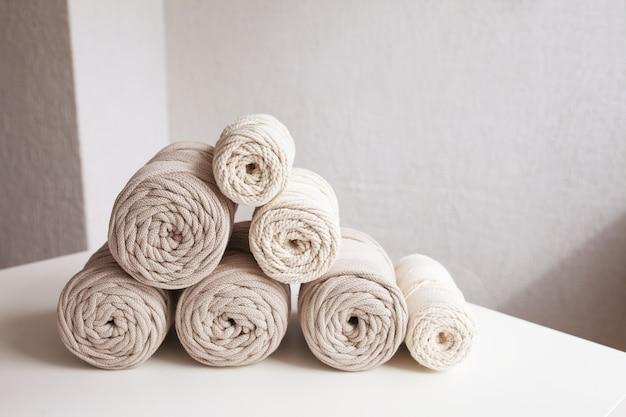 Handgefertigtes makramee-geflecht und baumwollfäden. hobby-strickgarnrolle aus baumwolle. natürliche baumwollkordel. weibliches hobby. platz kopieren