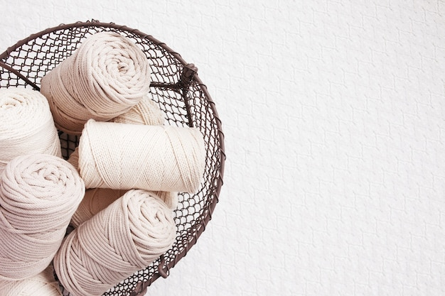 Handgefertigtes makramee-geflecht und baumwollfäden im korb