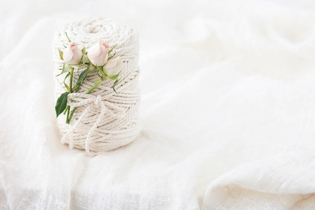 Handgefertigtes makramee-geflecht und baumwollfäden mit rosenblüte. bild gut für makramee- und kunsthandwerksbanner und werbung. ansicht von oben. platz kopieren