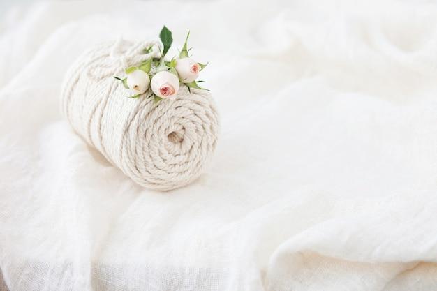 Handgefertigtes makramee-geflecht und baumwollfäden mit rosenblüten auf weißer bettwäsche