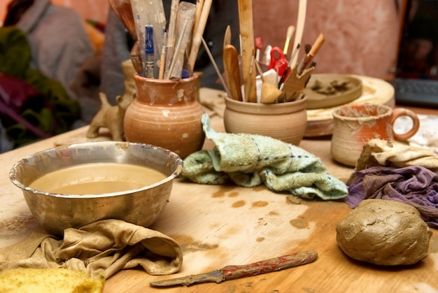 Handgemachte alte tontöpfe mit stiften und anderem zeug auf dem tisch