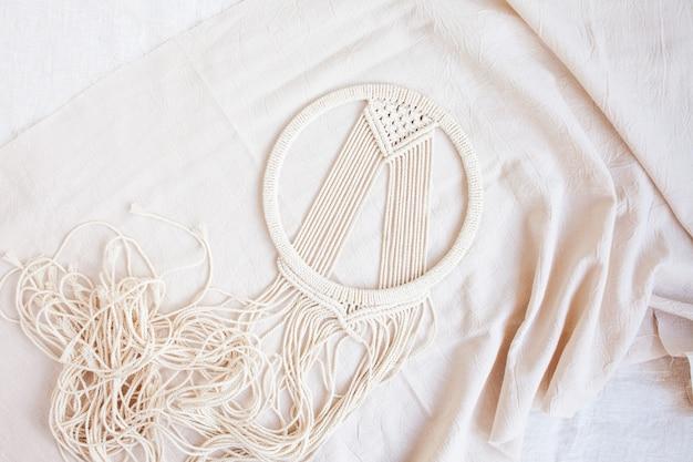 Handgemachte baumwolle makramee traumfänger während der herstellung. traditionelles amulett zum schutz des schlafes.