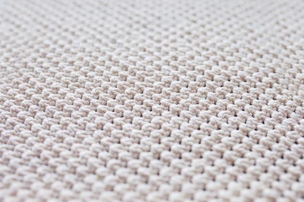 Handgemachte beige makramee. makramee-textur, eco-freundlich, modernes stricken. makramee-teppich auf holztisch