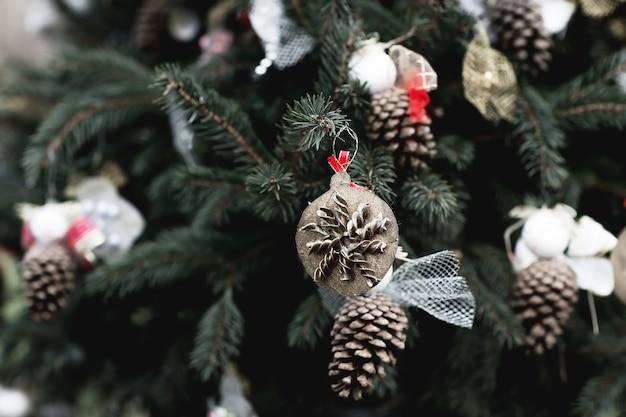 Handgemachte dekoration aus nudeln und tannenzapfen auf einem weihnachtsbaum-umweltkonzept