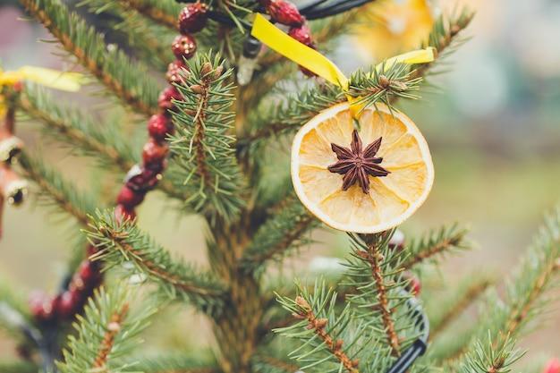 Handgemachte dekoration aus trockener orangenscheibe und anisstern am weihnachtsbaum