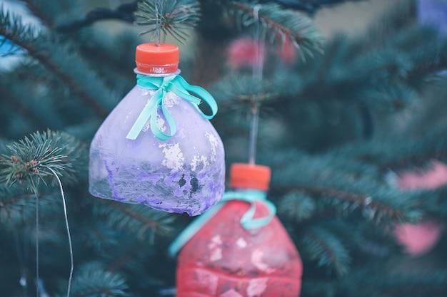 Handgemachte dekoration der wasserflasche auf weihnachtsbaum als recycling- und null-abfall-konzept