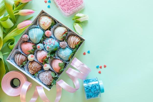 Handgemachte erdbeeren, blumen und dekoration mit schokoladenüberzug zum kochen des desserts auf grünem hintergrund mit freiem platz für text