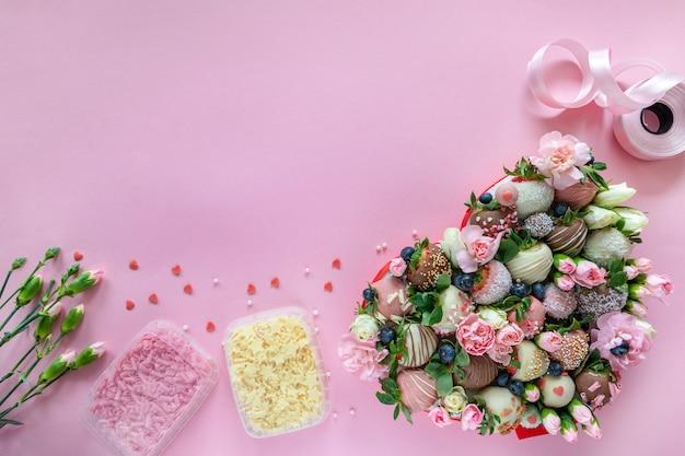 Handgemachte erdbeeren, blumen und dekoration mit schokoladenüberzug zum kochen des desserts auf rosa hintergrund mit freiem platz für text