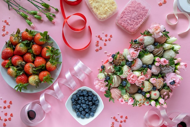 Handgemachte erdbeeren, blumen und dekoration mit schokoladenüberzug zum kochen des desserts auf rosa hintergrund