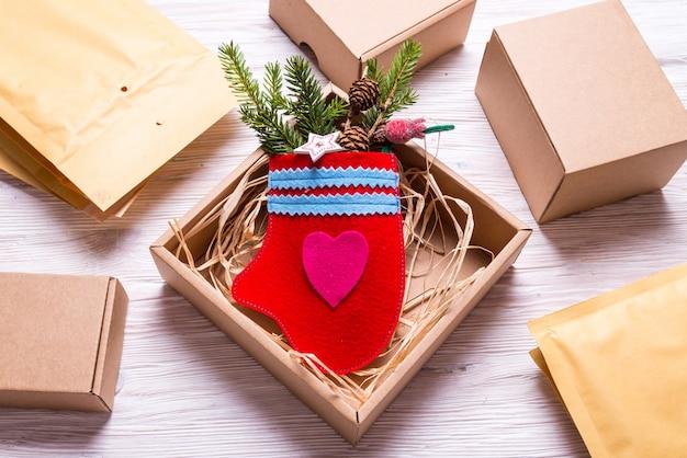 Handgemachte fäustlinge und postversender auf schreibtisch, weihnachtsgeschenkkonzept