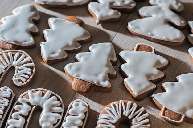 Handgemachte festliche lebkuchenplätzchen in form von sternen, personal, weihnachtsbäumen. auf einer leichten arbeitsplatte.