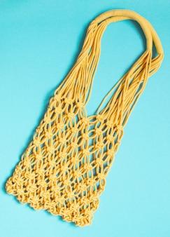 Handgemachte gelbe makramee-tasche auf hellblau, umweltfreundlich. modernes sommerstrandkonzept