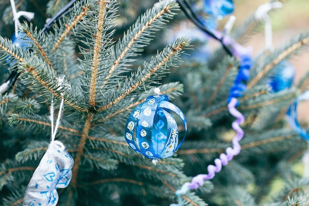 Handgemachte gemalte dekoration gemacht von der blauen plastikflasche auf einem weihnachtsbaum im freien.