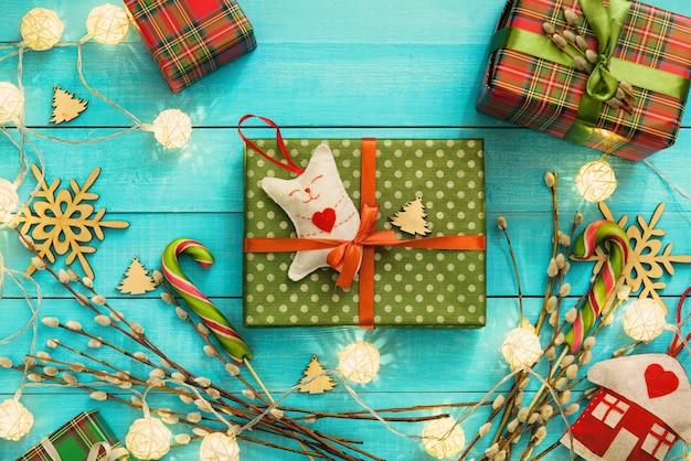 Handgemachte geschenkbox im roten band mit katzenspielzeug auf blauer holzoberfläche