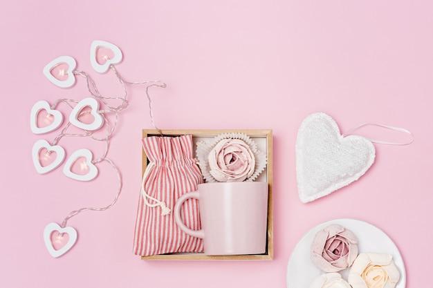 Handgemachte geschenkbox mit rosa tasse, marshmallow und überraschung in textiltasche, romantisches geschenk