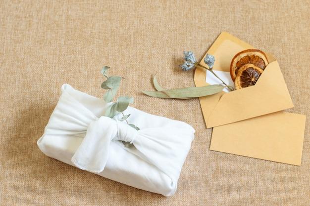 Handgemachte geschenkschleife umwickelte weiße kleidung im japanischen furoshiki-stil. umschläge mit kopierraum auf dem strukturierten hintergrund der sackleinen. null abfall, kunststofffreie geschenke, diy-konzept.